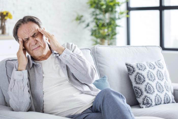 Uomo seduto sul divano con le mani portate alla fronte a causa di un attacco di acufene